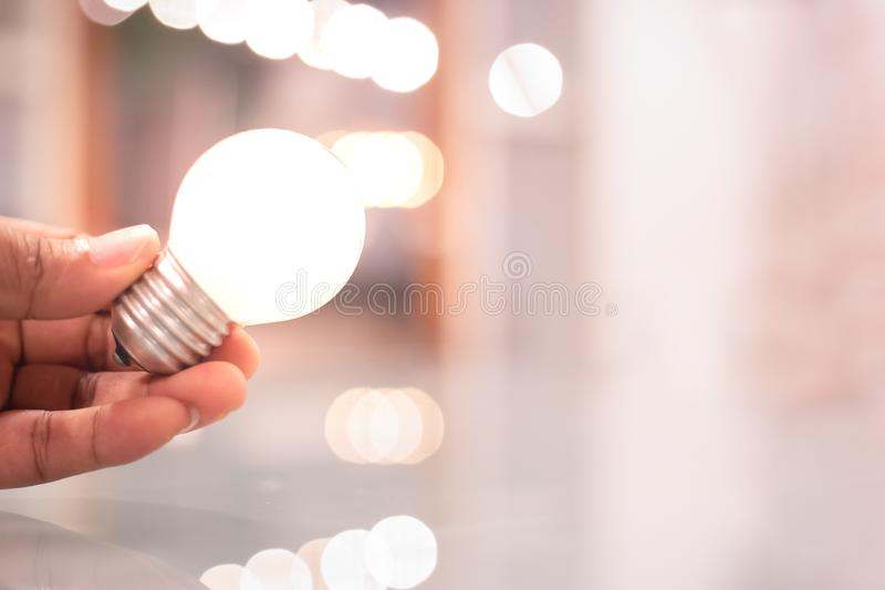 Save energy concept with light bulb holding in hand. Creative ideas for thinking symbol stock images