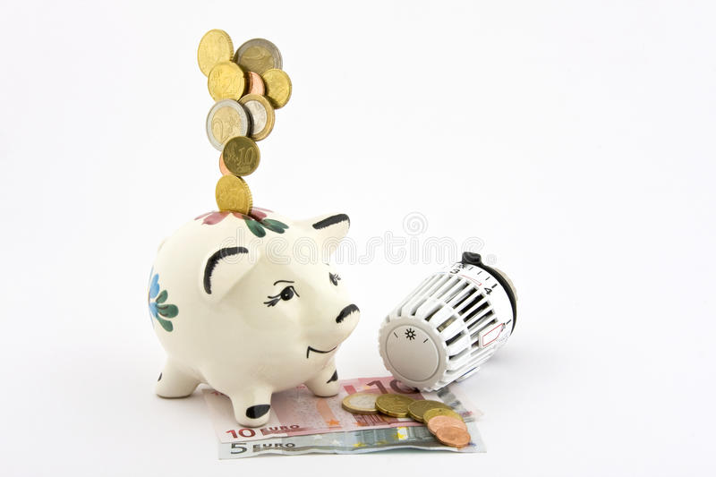 Save on heating costs. Coins falling into a piggy bank, which on paper money, coins are available on which a heater thermostat and imaged on a white background stock photos