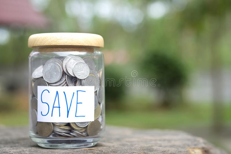 Save money concept with coin in bottle on bokeh background copy space royalty free stock photography