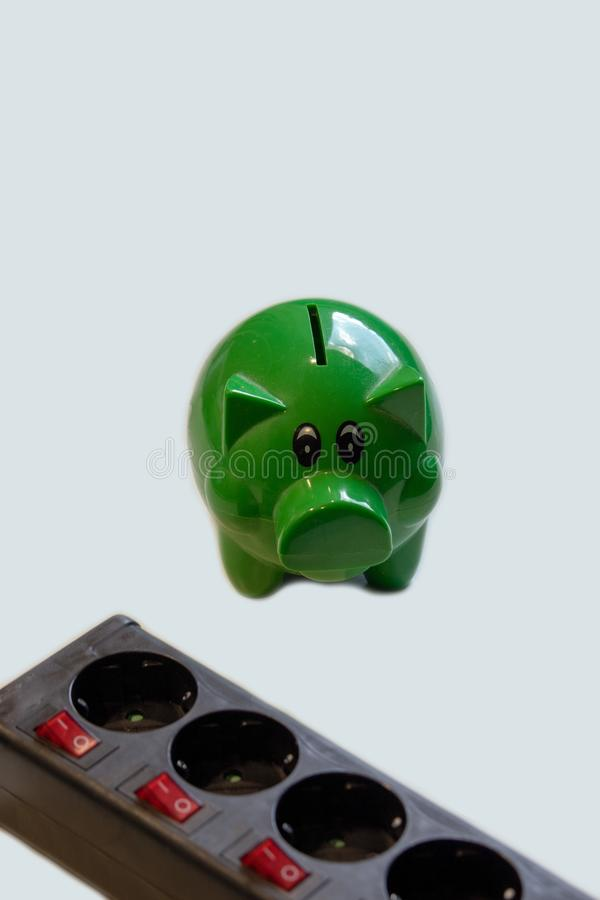 Save money with energy savings. Switchable socket power strip with green piggy bank with money.Save money with energy savings royalty free stock photos