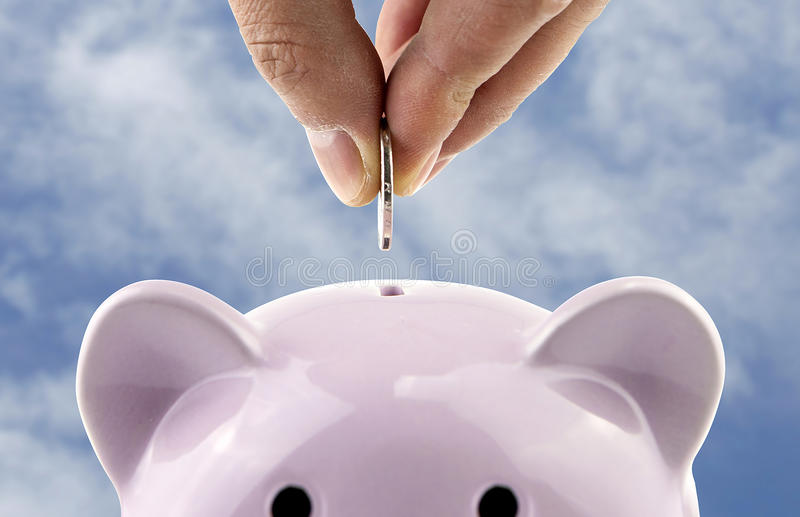 Save money. Into a piggy bank royalty free stock photography