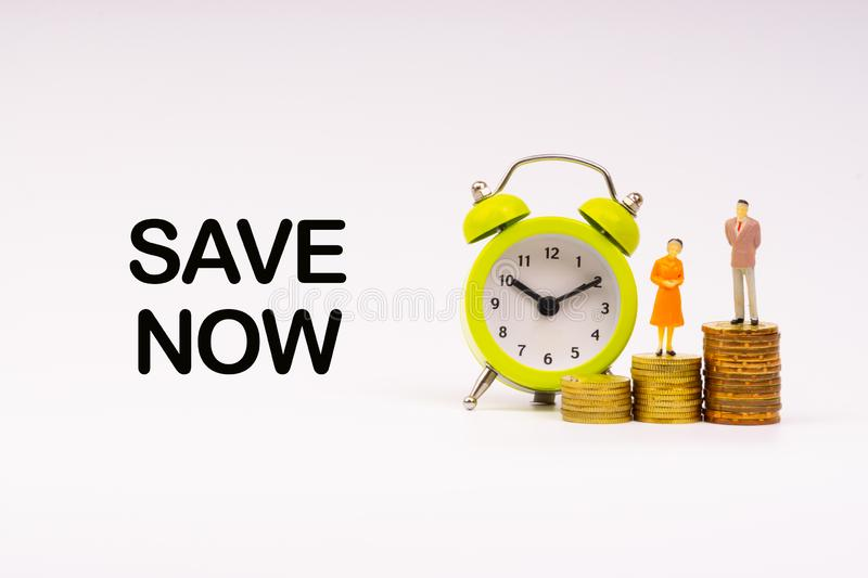 SAVE NOW inscription written, alarm clock, coins and businessman miniature royalty free stock photo