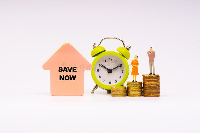 SAVE NOW inscription written, alarm clock, coins and businessman miniature stock images
