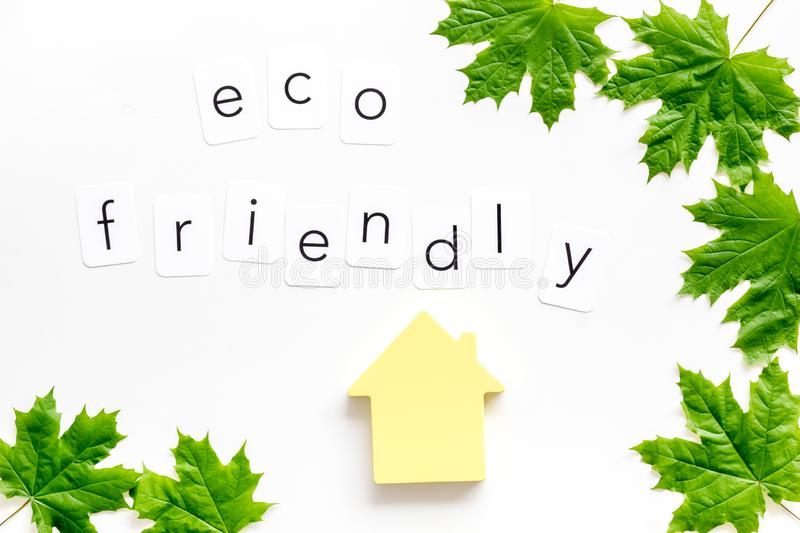 Green maple leaves, house figure and eco friendly text for ecology concept on white background top view. Save planet. Green maple leaves, house figure and eco royalty free stock photography