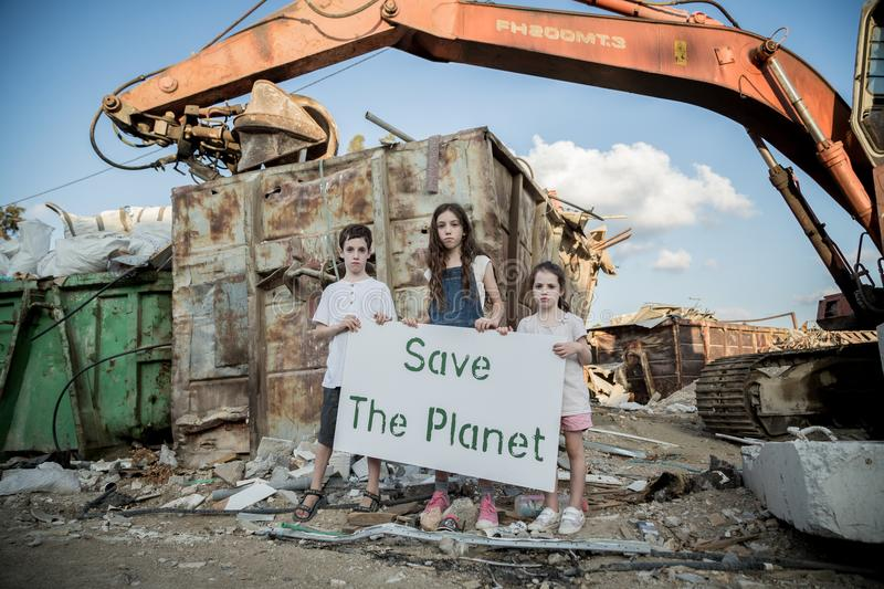 Save the planet. young kids holding signs standing in a huge junkyard. Save The planet. young kids holding signs for saving planet earth stock photography
