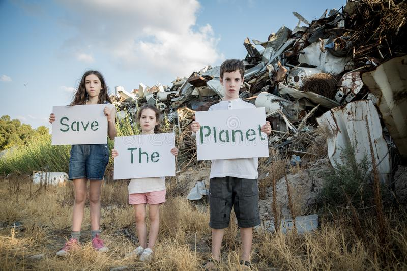 Save the planet. young kids holding signs standing in a huge junkyard. Save The planet. young kids holding signs for saving planet earth royalty free stock photography