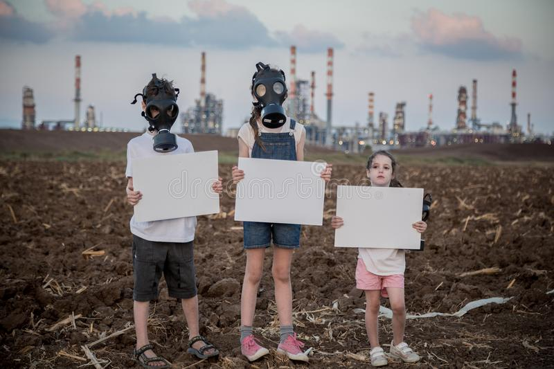 Save the planet. Young kids holding signs standing near a refinery with gas masks. Save the planet. young kids holding signs standing with gas mas stock photography
