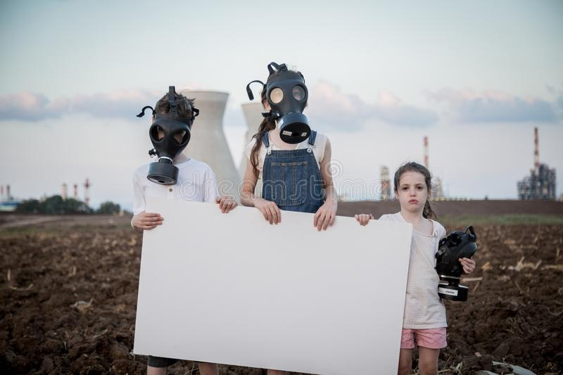 Save the planet. Young kids holding signs standing near a refinery with gas masks. Save the planet. young kids holding signs standing with gas mas stock images