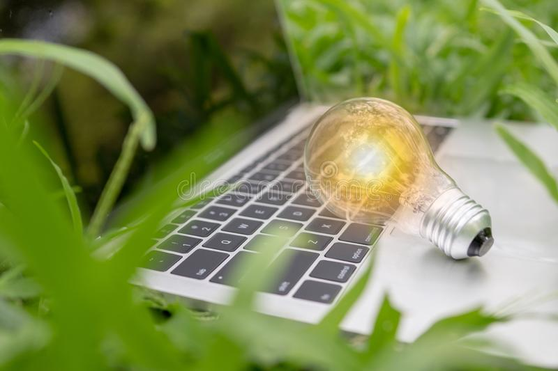 save power and good energy for nature concept ,light bulb on laptop in park stock photo