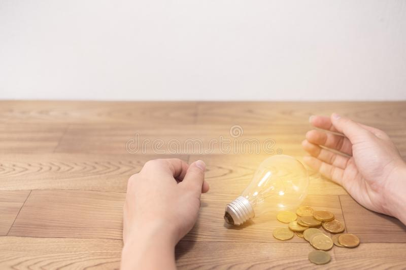 Save power to save the earth concept, young women hand put coins into light bulb on wooden backgrounds. stock photography