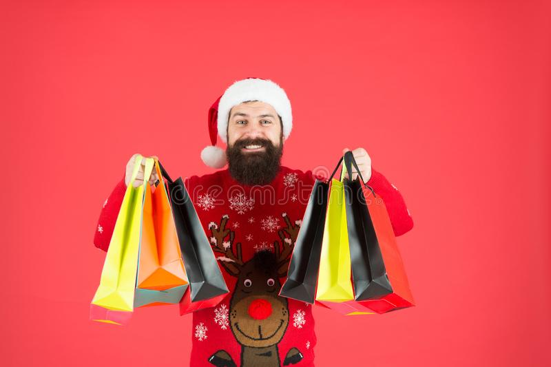 Save on purchases. Shopping with joy. Man bearded hipster wear winter sweater hold shopping bags. Buy new year gifts stock photography