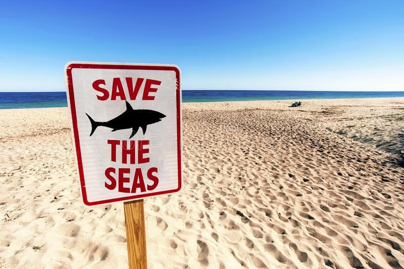 Save the Seas Sign. On Sunny day in Summertime at Sandy Beach royalty free stock image