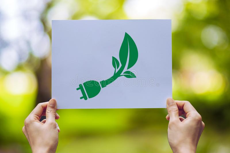 Save world ecology concept environmental conservation with hands holding cut out paper power plug showing. Nature, green, design, natural, background, creative stock photo