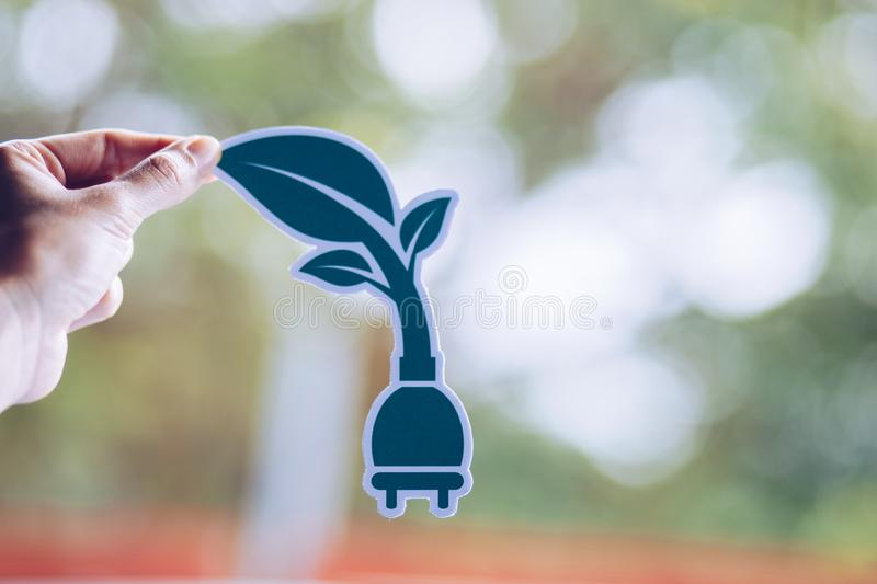 Save world ecology concept environmental conservation with hands holding cut out paper power plug showing. Nature, green, design, natural, background, creative royalty free stock image
