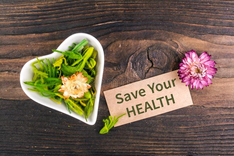 Save your health text on card. With dried flower and heart shape bowl on wood royalty free stock image