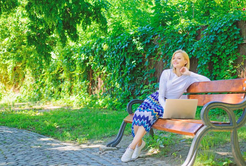 Save your time with shopping online. Shopping online. Girl sit bench with notebook. Woman with laptop in park enjoy. Green nature and fresh air. Girl dreamy stock images