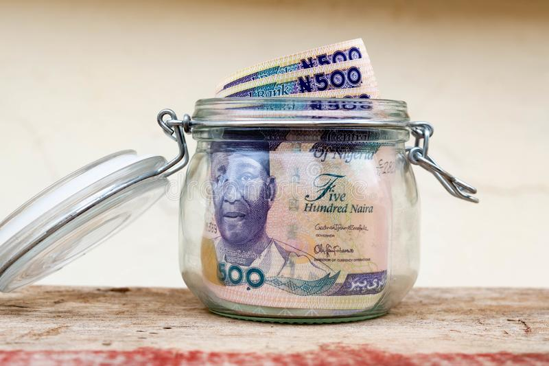 Saved five hundred naira notes savings jar with some notes sticking out of the top of the open jar for banking, insurance, savings royalty free stock images