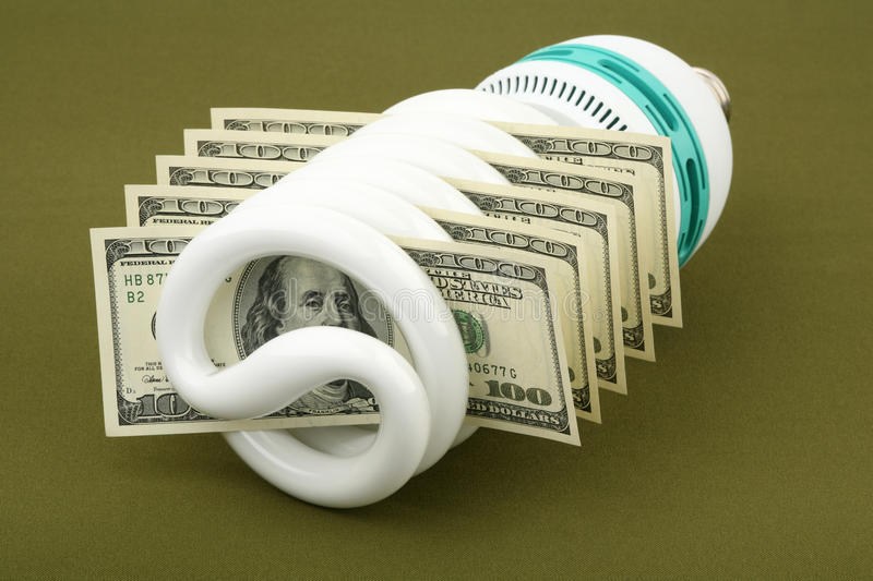 Saved money. Fluorescent lamp and US dollars on a green background royalty free stock images