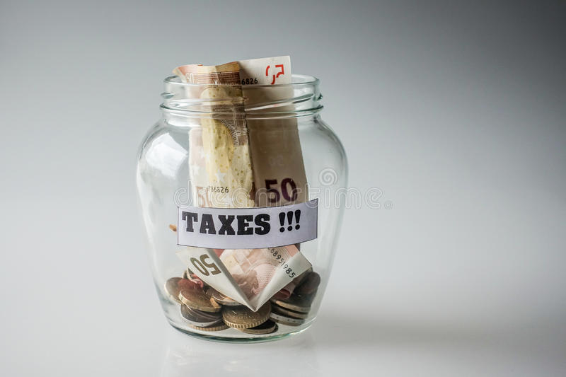 Saved money for taxes. In a glass jar stock images