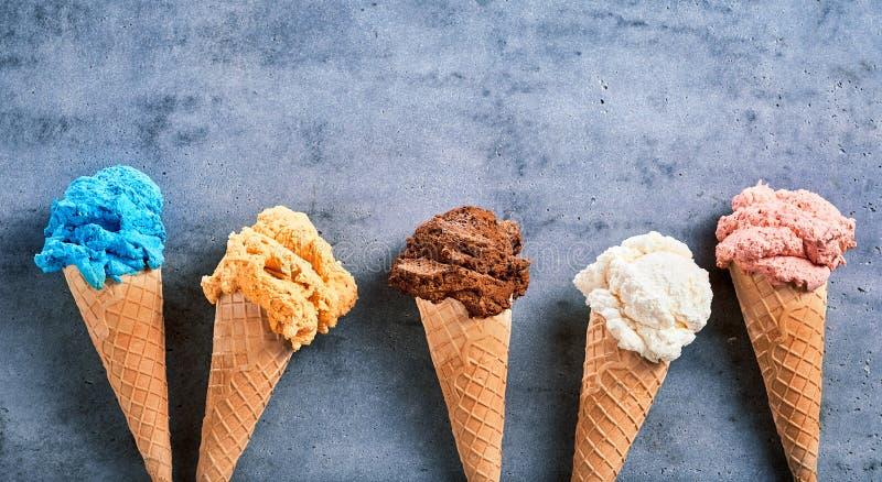 Saveurs assorties de crème glacée dans les cônes dans une bannière photos stock