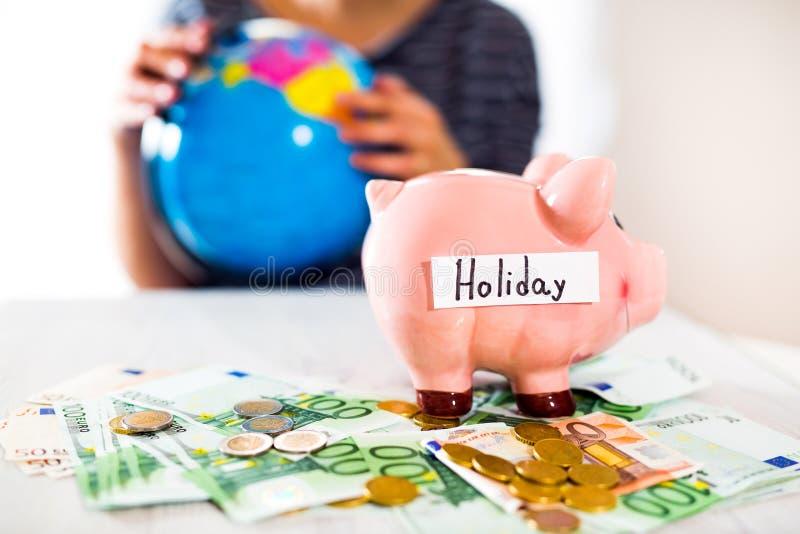 Saving concept. Piggy bank with an inscription holiday. Woman holding a globe. Selective focus stock photos