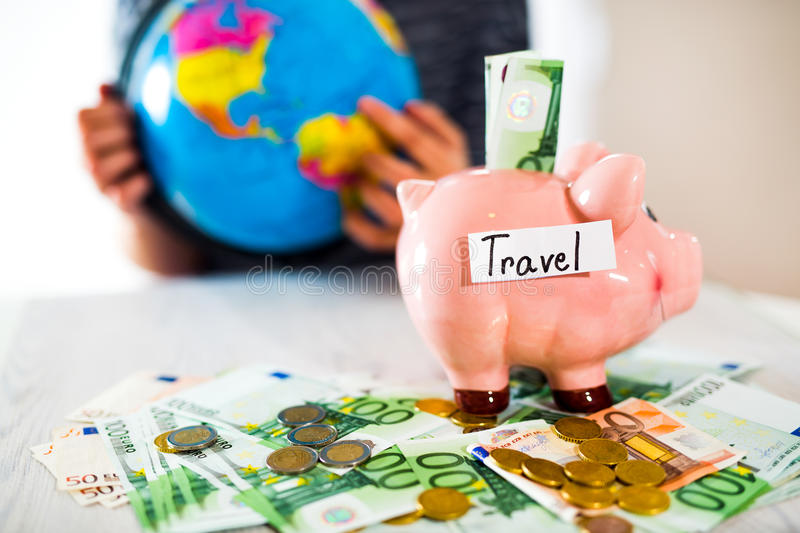 Saving concept. Piggy bank with an inscription travel. Woman holding a globe. Selective focus stock image