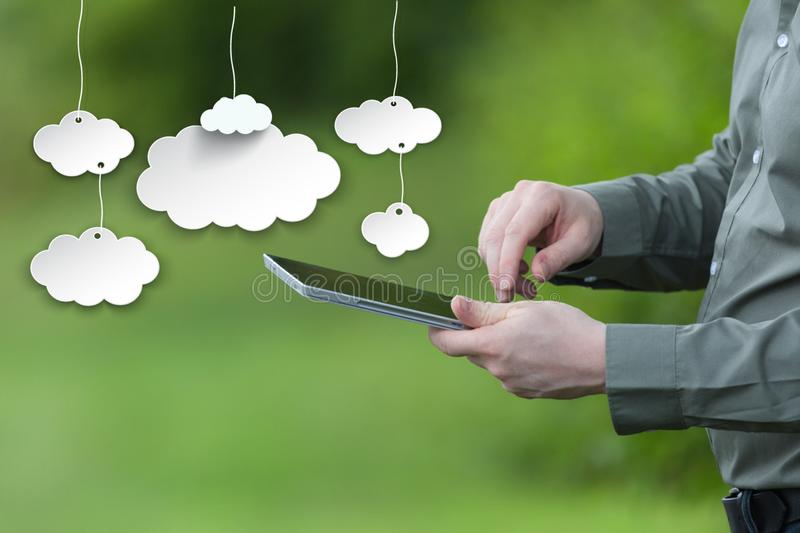 Saving data on the cloud concept. Businessman holding a smart tablet, mobile green background stock image