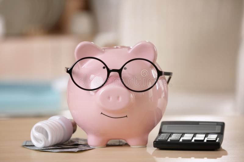 Saving electric power concept. Ceramic piggy bank. With calculator and money on table stock image