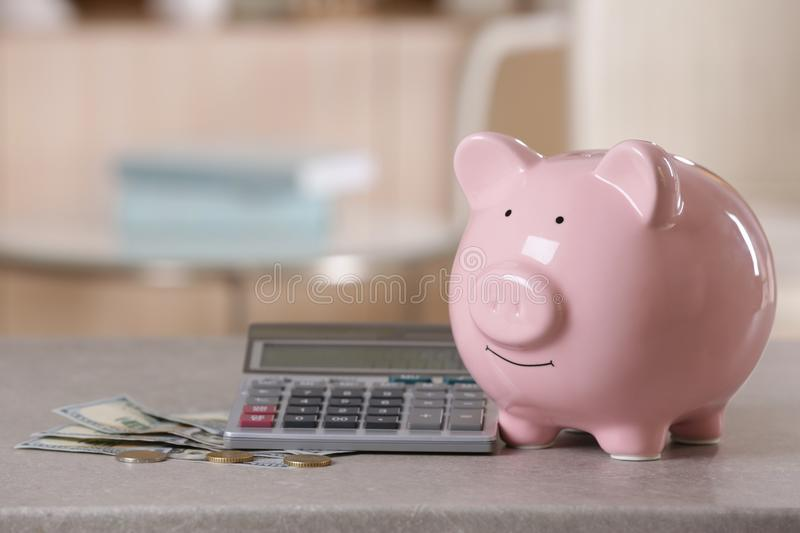 Saving electric power concept. Ceramic piggy bank. With calculator and money on table royalty free stock photography