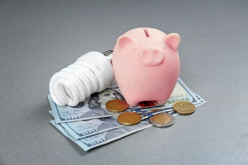Saving electric power concept. Ceramic piggy bank. With money on grey background stock images