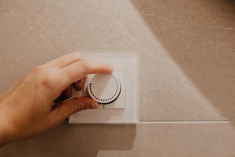 Saving energy concept: Human hand turning down electrical light dimmer switch royalty free stock photography
