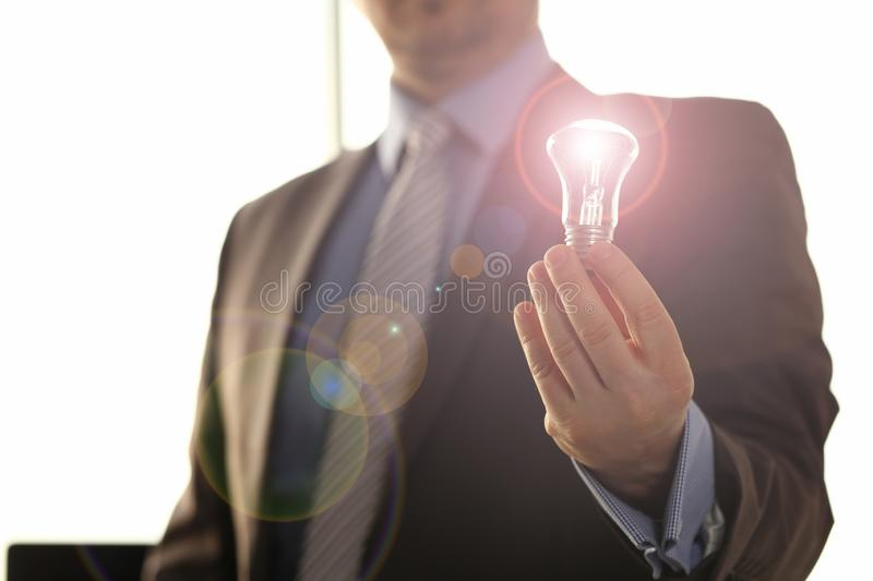 Saving Energy New Solution Innovation Technology. Businessman in Suit Hold Traditional Light Bulb. Male HR Executive Manager with Lamp in Hand. Creative stock image