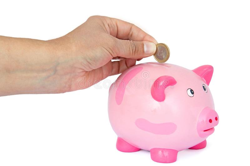 Hand dropping euro into a piggy bank stock images
