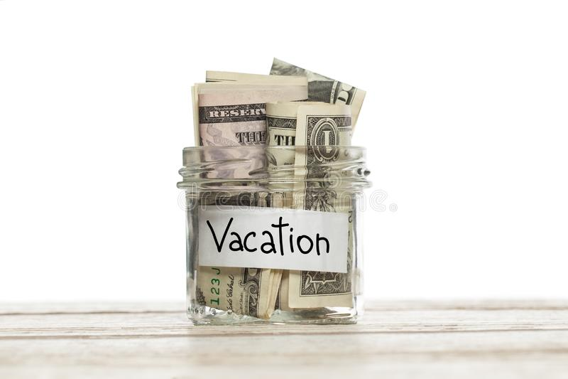 Saving glass jar with money for vacation on wooden table against white background stock photo