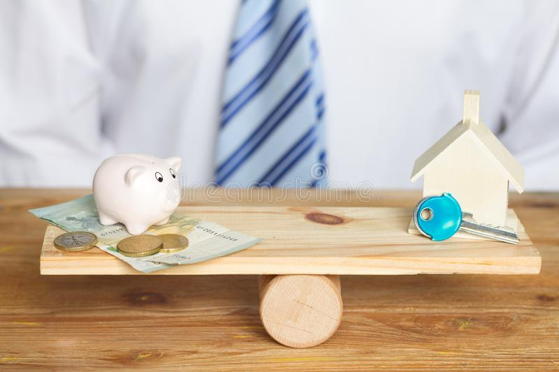 Saving for a house and balance concept with money and piggy bank on a swing. Closeup royalty free stock photography