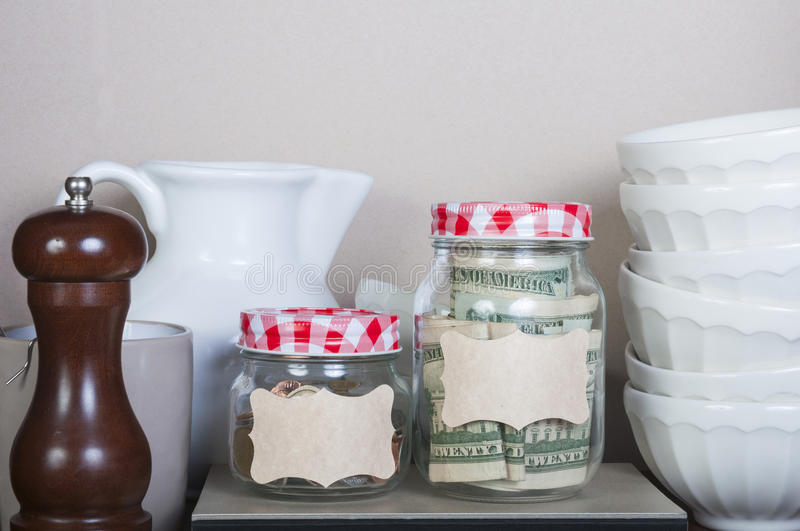 Saving Mom. Two bottles with labels filled with money on a cookbook royalty free stock photography