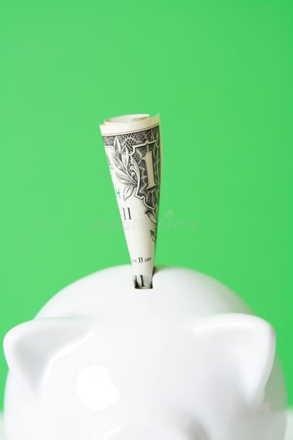 Saving money. Depositing a dollar into a piggy bank stock photography