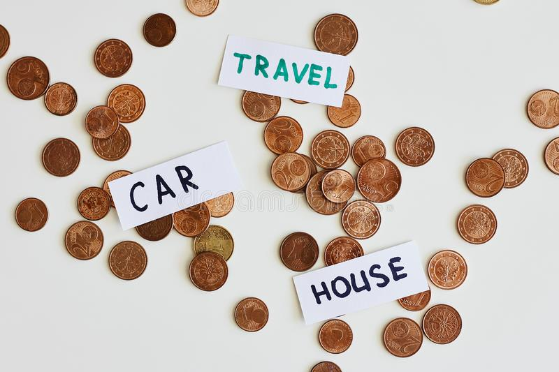 Saving money for the best life concept. Coins and signs travel, car, house stock photo