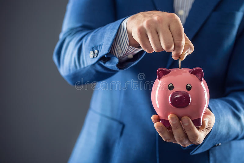 Saving money. Businesman holding pink piggy and putting coin into piggy bank stock images