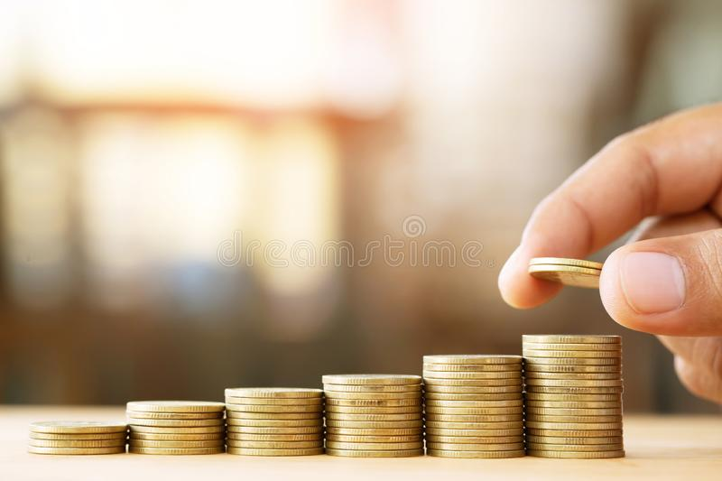 Saving money. businessman hand putting stack coins to show concept of growing savings money finance business and wealthy. stock image