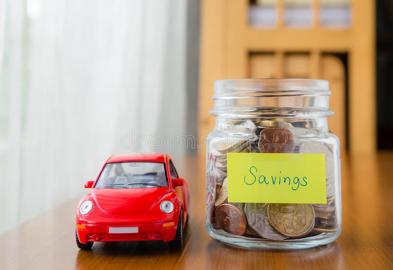 Saving money for a car. Many world coins in money jar with savings label on jar and a red car model, concept to financial planning for car loan royalty free stock photos