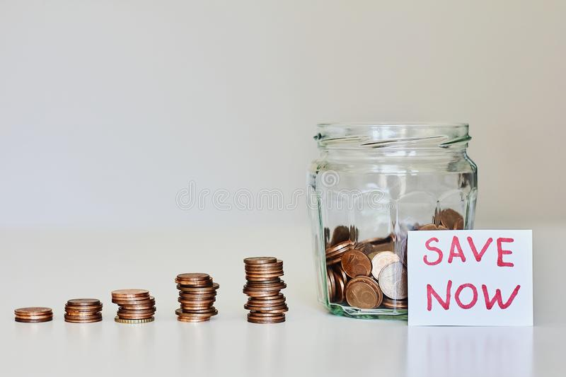 Saving money concept. Glass jar full of coins, stacks of coins and sign save now royalty free stock images