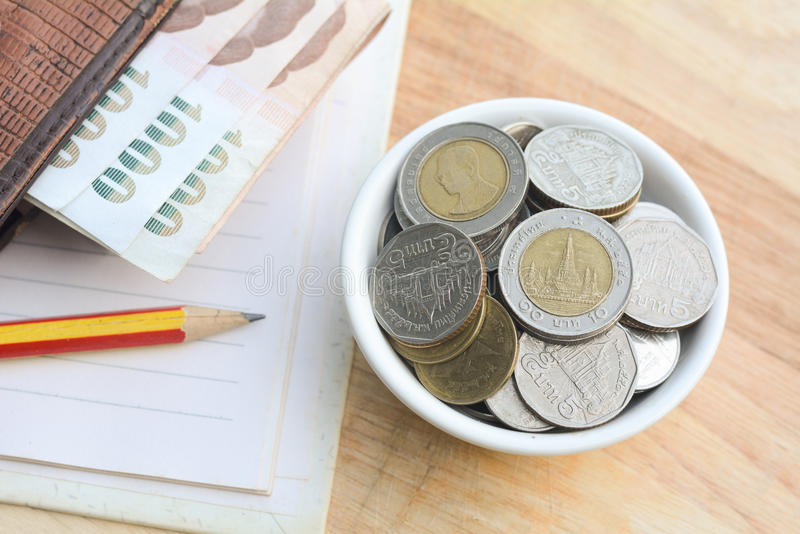 Saving money concept. Putting coins in a cup on a wooden floor stock photos