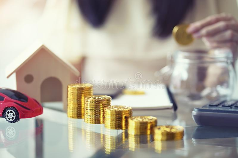 Saving money concept, Stack of gloden coin with wooden house and red car mortgage, woman hand putting coins in jug glass royalty free stock images