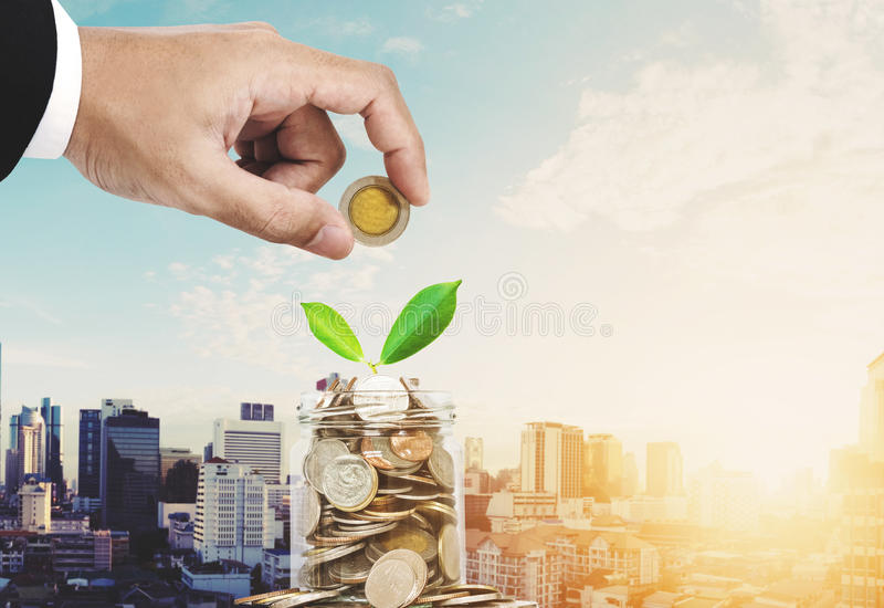 Saving money concepts, businessman hand putting coin in glass jar container, with plant bud glowing, on Bangkok city in sunrise royalty free stock image