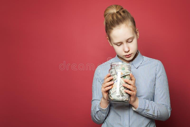 Saving money. Cute teen girl holding jar with money cash royalty free stock photos
