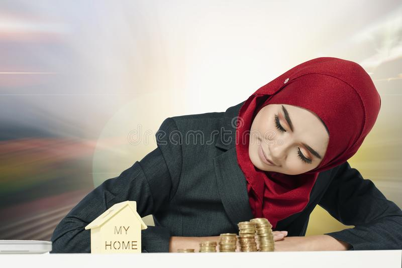 Saving money for dream home, young woman look at miniature house over abstract background stock photography