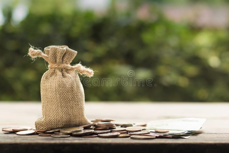Saving money for future, home, car, education, investment, descendants concept : Money bag with many coins on wood table with. Green nature as background. Copy stock images