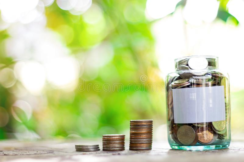 Saving money in a glass bottle. The background is green trees bokeh royalty free stock images