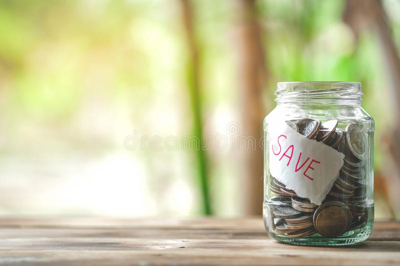 Saving money with hand putting coins in jar glass, save and investment money for prepare in the future. Saving financial concept royalty free stock image